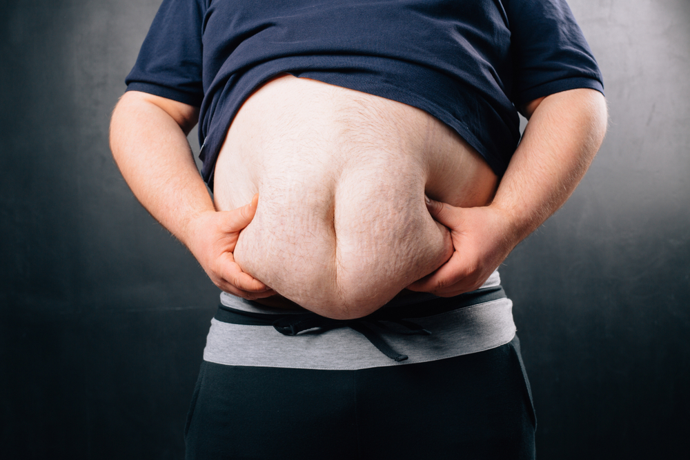 man grabbing fat rolls