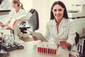 beautiful medical HGH doctor in protective glasses is working with test tubes microscope and digital  300x200