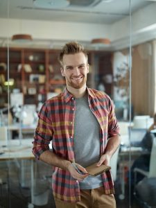 storyblocks portrait of cheerful handsome man wearing colorful checkered shirt smiling to camera standing by glass wall in modern office_BT7xL7T7bf 225x300